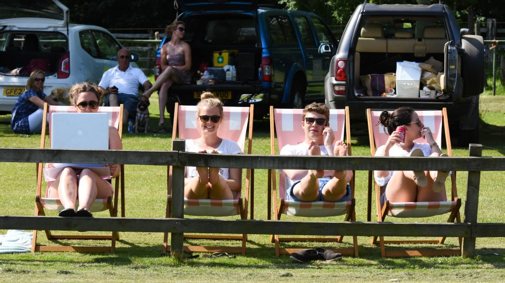 people sat on deck chairs watching polo