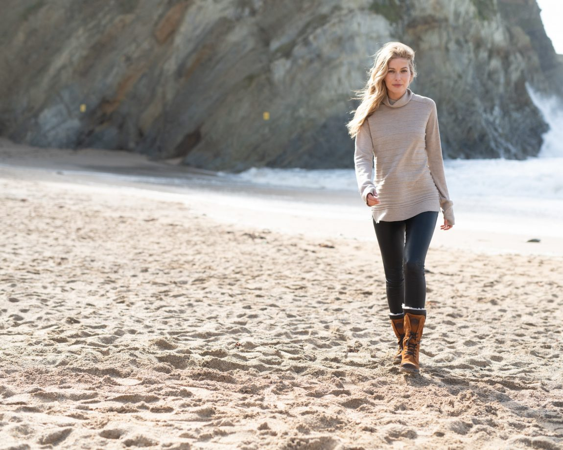 woman walking along beach in celtic and co